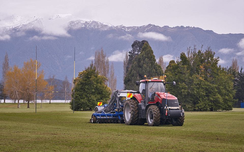 Red tractor pulling cultivation equipment across a rugby field.