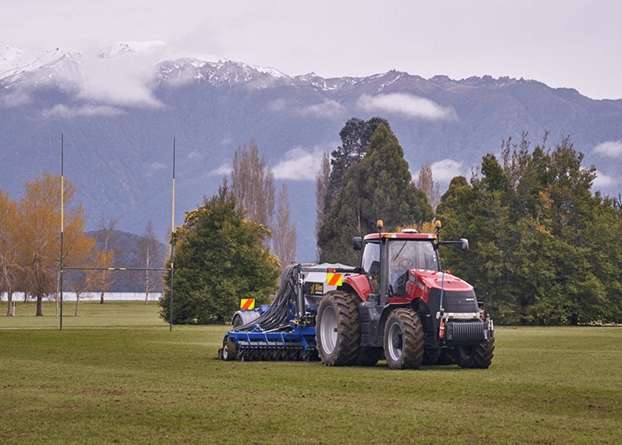 Tractor pulling direct drilling equipment at Te Anau Rugby Club field