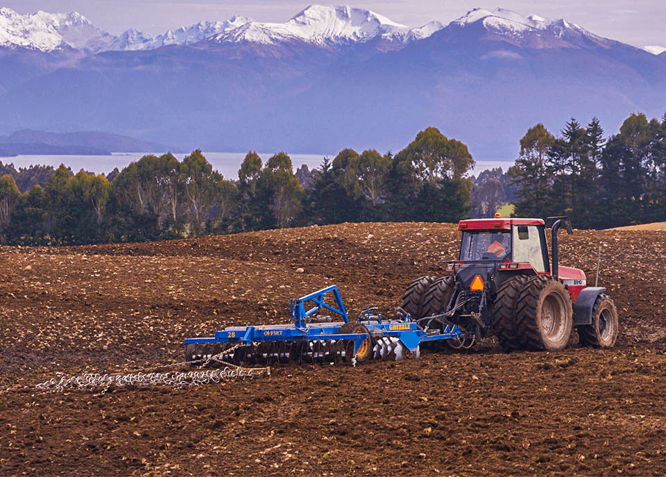 Red tractor pulling Grizzly Discs through soil in a paddock