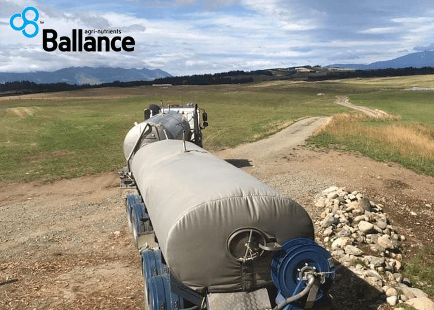 Large truck hauling fertiliser through a field