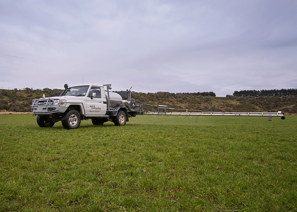 White truck using controlled booms to spray paddock
