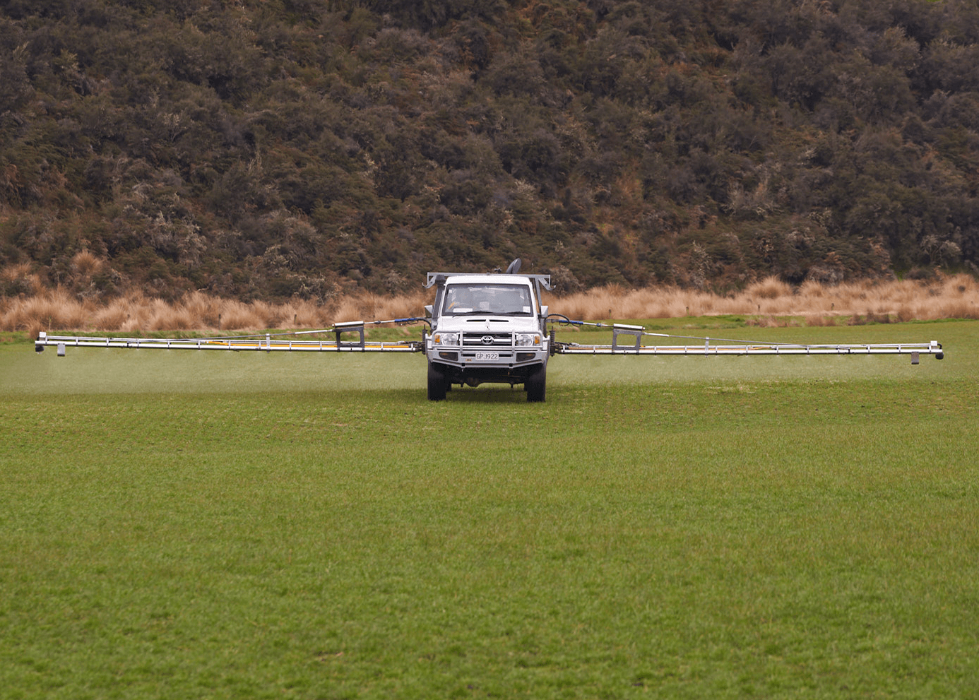 Walsh Contracting Te Anau Limited White Truck front on perspective with controlled booms doing a sprayout